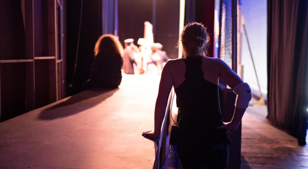 Female student sitting backstage with her back to the camera and stage lights flooding past her